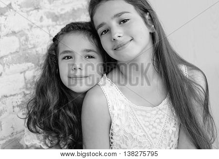 Two cute little sisters huddled together on a white background ( black and white )