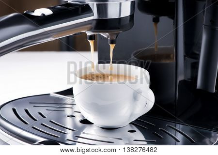 Close-up of espresso pouring from coffee machine. Preparation for design creative menu.