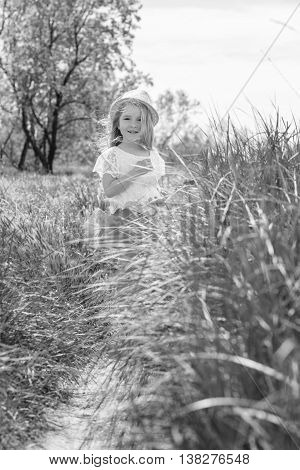 happy little girl walks outdoors in the summer ( black and white )