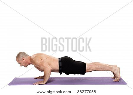 Fitness trainer doing pushups on a yoga mat