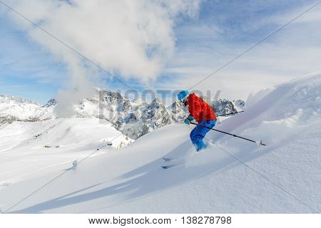 Skier skiing downhill in high mountains, San Martino di Castrozza in Italy