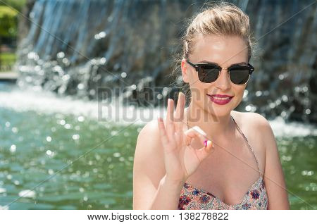 Lady With Sun Glasses Outdoor Showing Okay Gesture