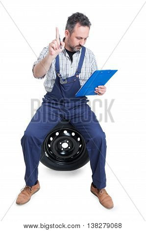 Busy Engineer On Garage Writing On Clipboard