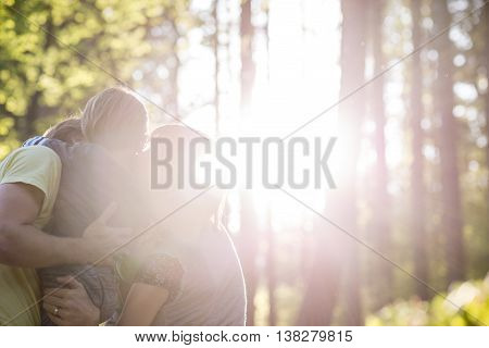 Family embracing in woods back lit by bright sunlight beaming through tall trees with copy space.
