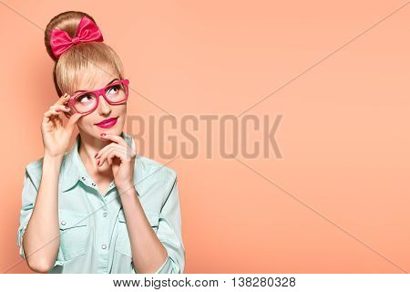 Fashion. Woman in Stylish Glasses Having Fun. Hipster fashion girl think, idea. Playful nerd Blonde with Glamour Pinup Stylish hairstyle, Trendy fashion, red bow Makeup. Unusual Creative, on yellow