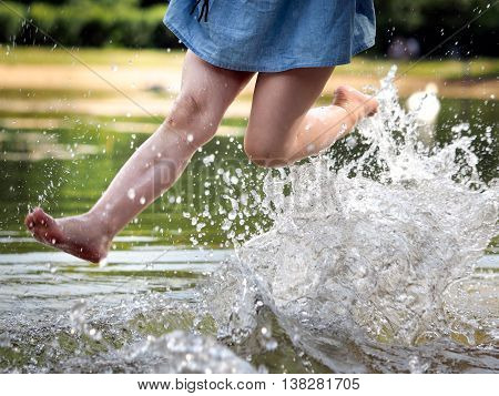 Feet small girl above water. River, spray, lots of sun. Concept - rest by the water, swimming, child's happiness, hot summer