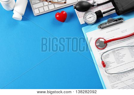 Medical concept. Medical stethoscope and manometer with patient history on blue background