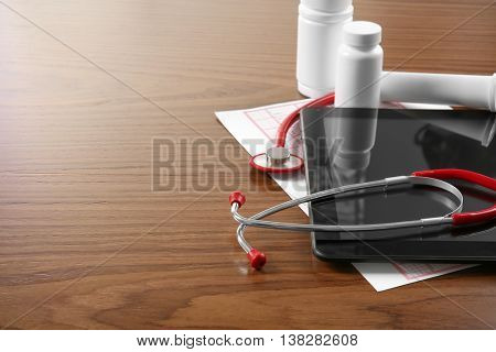 Medical concept. Medical stethoscope, pills and tablet on a wooden background