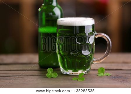Glass of green beer with clover leaves and bottle on wooden table