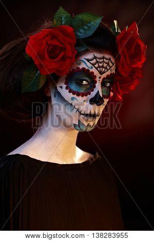 Woman wearing mexican santa muerte makeup, looking at camera.
