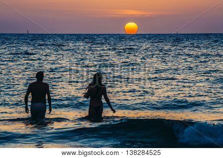Tel Aviv Israel - October 21 2015. Couple walks in the sea against the backdrop of the setting sun in Tel Aviv