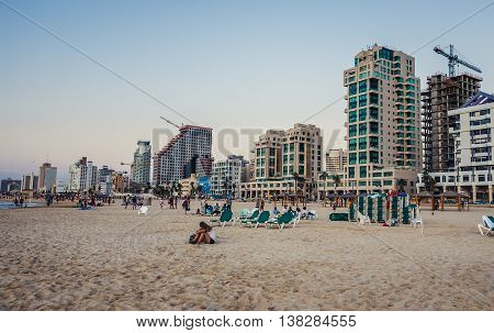 Tel Aviv Israel - October 21 2015. People on the beach in Tel Aviv. View with hotels and residential building situated along the coast