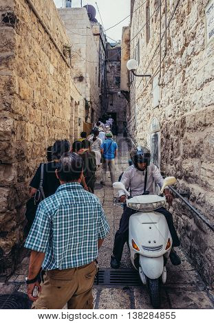 Jerusalem Israel - October 22 2015. Man rides a motor scooter between pedestrians on the street of Jewish Quarter