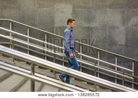 A man goes down the stairs. Side view