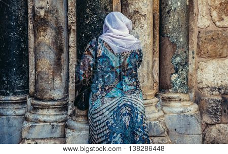 Jerusalem Israel - October 22 2015. Woman prays in front of the wall of Church of the Holy Sepulchre located in Christian Quarter