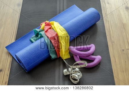Selection of colorful home gym equipment on yoga mat against wooden floor background