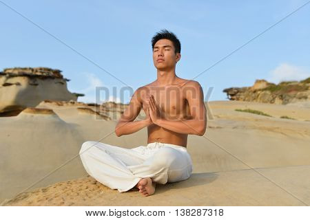 young Man muscular man doing yoga exercise in outdoors