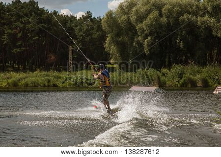 Man Wakeboarding on a river in summer