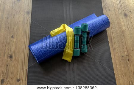 Hand weights resistance band and yoga mat on black foam mat on wooden floor background
