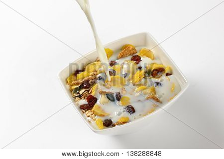 milk pouring into bowl of corn flakes and cereals on off-white background with shadows - close up