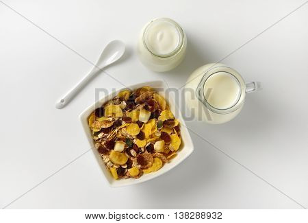 bowl of oat flakes with jug of milk and glass of white yogurt on off-white background with shadows