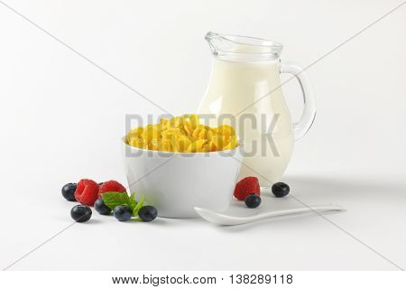 bowl of corn flakes and jug of milk on on off-white background with shadows