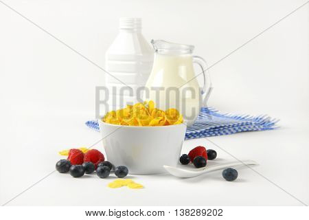 bowl of corn flakes and jug of milk on checkered dishtowel