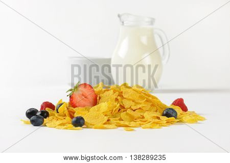 jug of milk and corn flakes with berry fruits on white background