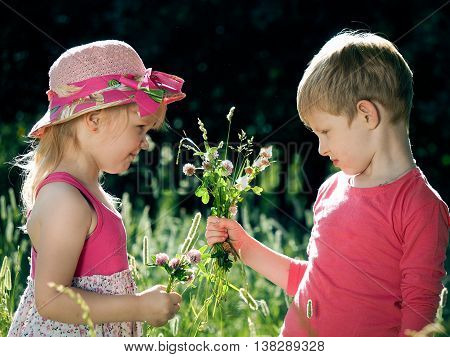 Small children with flowers. The boy gives flowers to the girl. Stunning facial expression vivid emotions on their faces. Summer heat green grass and a lot of sun