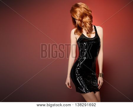 Fashion woman in Glamour Sequin black dress. Stylish Luxury party Outfit. Playful redhead sexy Model girl, Trendy wavy Hairstyle on red. Fashion Makeup, shiny Accessories. Unusual creative