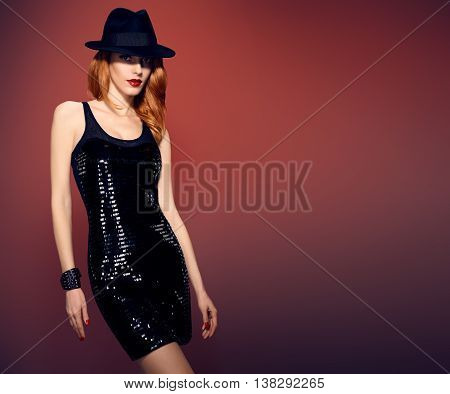 Fashion woman in Glamour Sequin black dress. Stylish Luxury party Outfit. Playful redhead sexy Model girl in hat, Trendy wavy Hairstyle on red. Fashion Makeup, shiny Accessories. Unusual creative