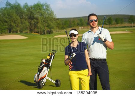 Portrait of young sportive gouple golfers playing golf at sunny day
