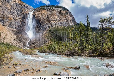 Autumn  Takakkaw Falls forms a full-flowing water flow of pearl color. Yoho National Park. Rocky Mountains of Canada