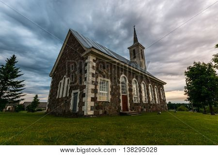 Old catholic church building with nature landscape. Epic sky with massive clouds. Stormy weather.