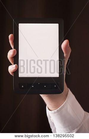 An ebook reader in a hand on a dark background