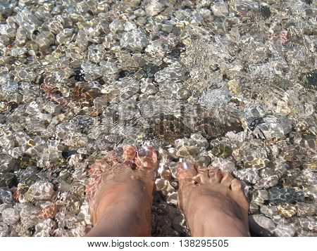 Feet in a clean water with bottom with pebbles on the Garda lake in Italy