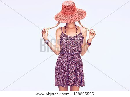 Fashion Hippie Boho woman Having Fun. Playful Model, Summer Fashion Boho Outfit. Blonde in Trendy Sundress, pigtails, Fashion Accessories. Hat covers girl face, romantic fashion Style.Unusual creative