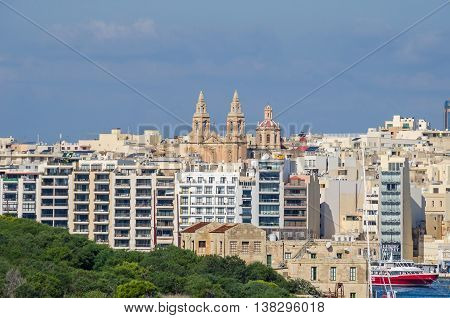 Gzira Malta - November 8 2015: View of Gzira a town located in Marsamxett Harbour as seen from Valletta. Old Cathedral surrounded by densely built-over modern buildings.