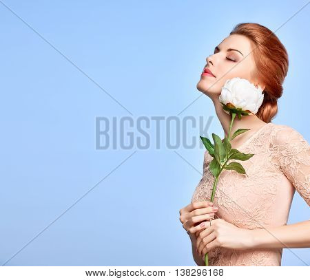 Fashion Natural Makeup. Beauty portrait woman in Fashion dress. Redhead Model girl with flower, Hairstyle, Makeup. Green Eyes, Eyelashes, Perfect skin. Skincare concept. Creative unusual look