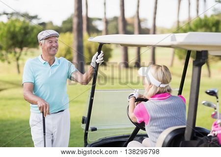 Smiling mature man looking at woman sitting in golf buggy