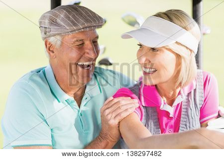 Cheerful golfer couple sitting in golf buggy