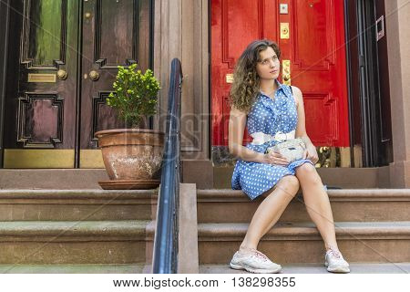 Red and black doors and young woman with blue polka dot dress sitting on porch in a city