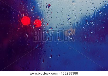 The glass of the window with rain drops and red lights in Edinburgh Scotland.
