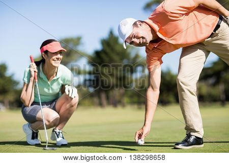 Portrait of man removing golf ball from hole while woman crouching on field