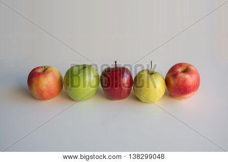 Five different apple varieties on light background