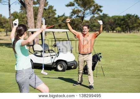 Happy golfer couple with arms raised while standing on field