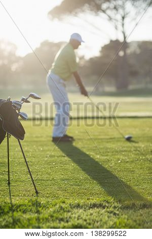 Full length of man playing golf while standing on field during sunny day