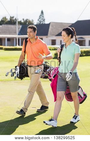 Full length of couple carrying golf bags while walking on field