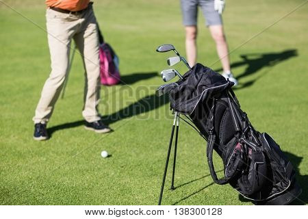 Low section of couple playing golf with bag on foreground