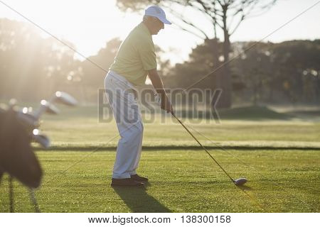 Full length side view of mature man playing golf while standing on field